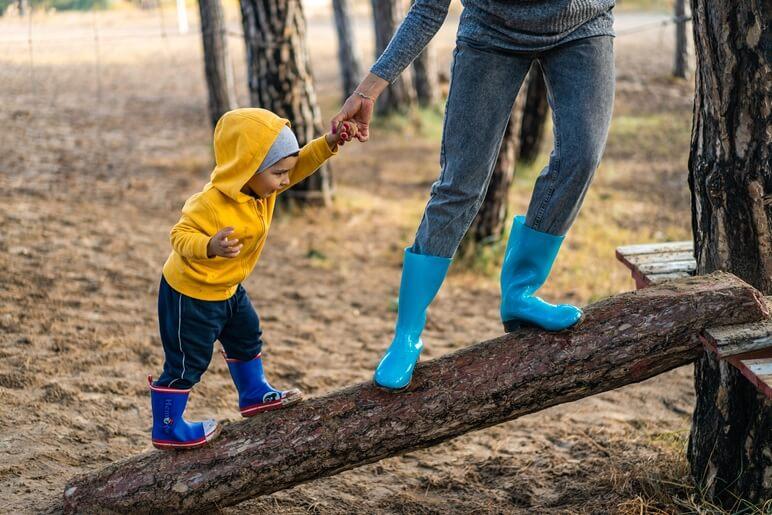 parent and child climbing a wooden log